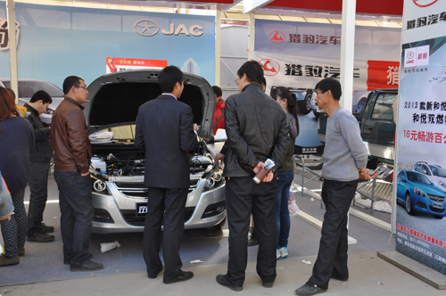 江淮汽车经销商现场人员为客户讲解双燃料汽车.高清图片